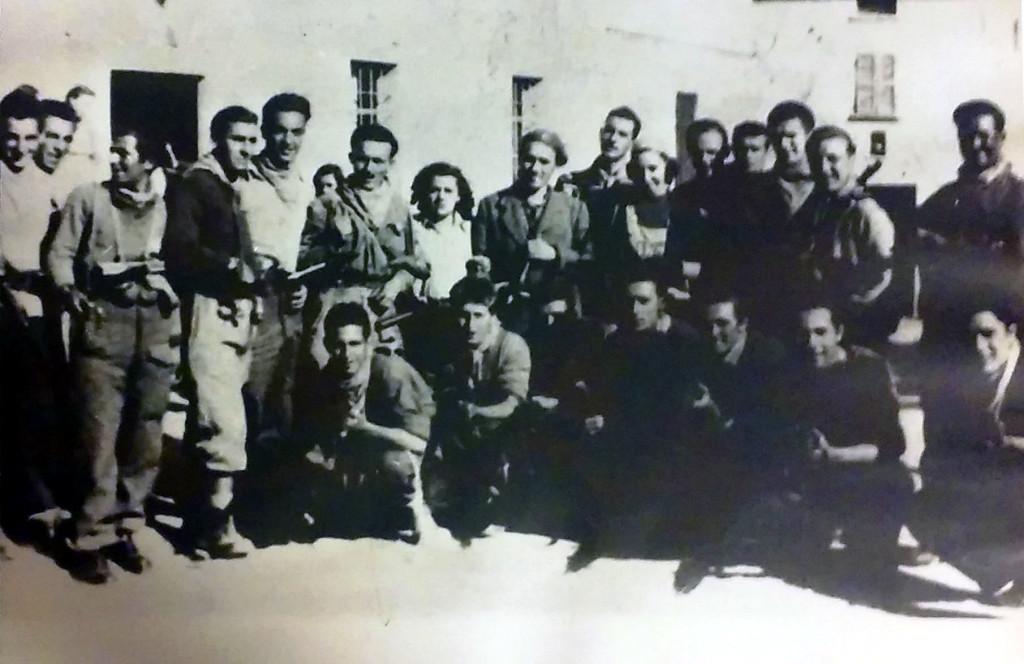 """Foto di gruppo della Brigata """"Muccini"""" dopo la Liberazione di Bardi: primo da destra in piedi è Barbieri (""""Ninon""""), terzo da destra in piedi è Flavio Bertone """"Walter"""", il quinto è Paolino Ranieri """"Andrea"""", l'undicesimo da destra Turiddu Perugi """"Rì"""", il tredicesimo da destra Socrate Benacci. Fra i seduti: il primo da sinistra è Renato Lorenzetti """"Ottavio"""" , il secondo da sinistra Giovanni Venturini """"Guido"""" - Archivio I.S.R. La Spezia (l'identificazione dei partigiani è avvenuta anche seguendo p.145 di La provincia della Spezia, medaglia d'oro della Resistenza, Edizioni Giacché, 1997)"""